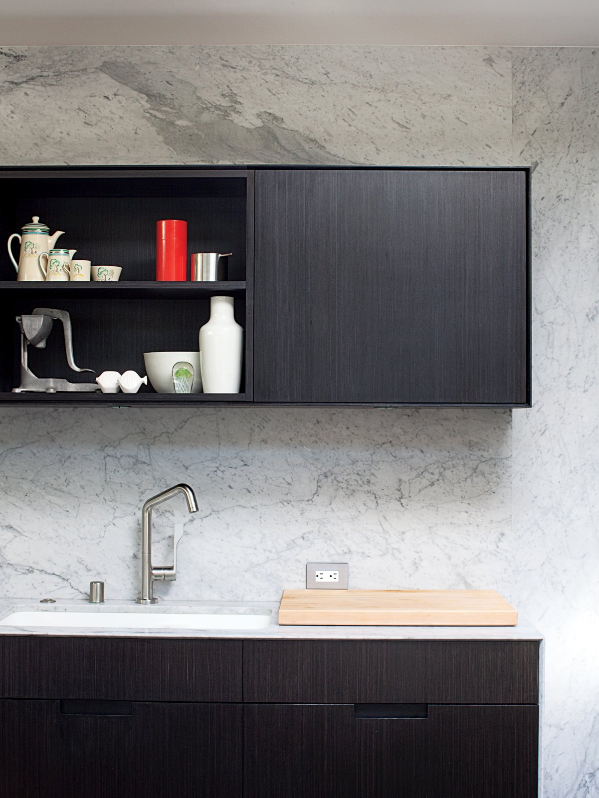 Carrera marble as covers this whole wall. The cabinets are floating which look great, but the finish on the cabinets have been tough to keep looking good!  The Deam House by Lara Deam