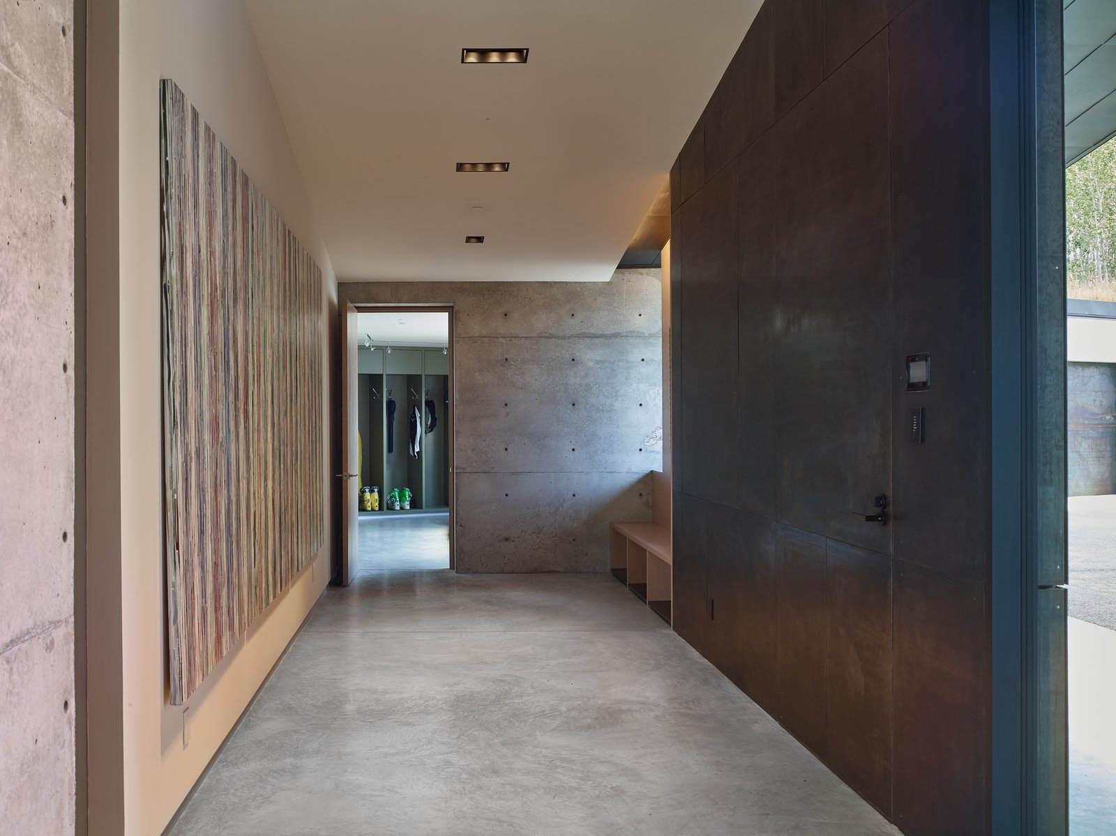 Hallway and Concrete Floor The client possessed a collection of art to be placed in the home, which was meticulously considered in the design process. Drywall was used exclusively and deliberately to hang the artwork to each piece's necessary measurement.   Wyoming Residence by Abramson Teiger Architects