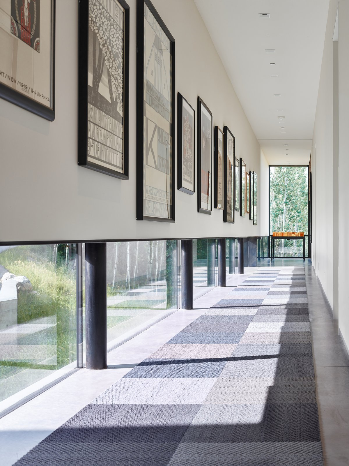 Hallway, Rug Floor, and Concrete Floor An art gallery was designed with low windows to allow natural light to permeate while protecting the sensitive art from harmful direct sunlight. It is these careful details that, in combination with the striking lineation of the home, create a harmonious alliance of function and design.  Wyoming Residence by Abramson Teiger Architects