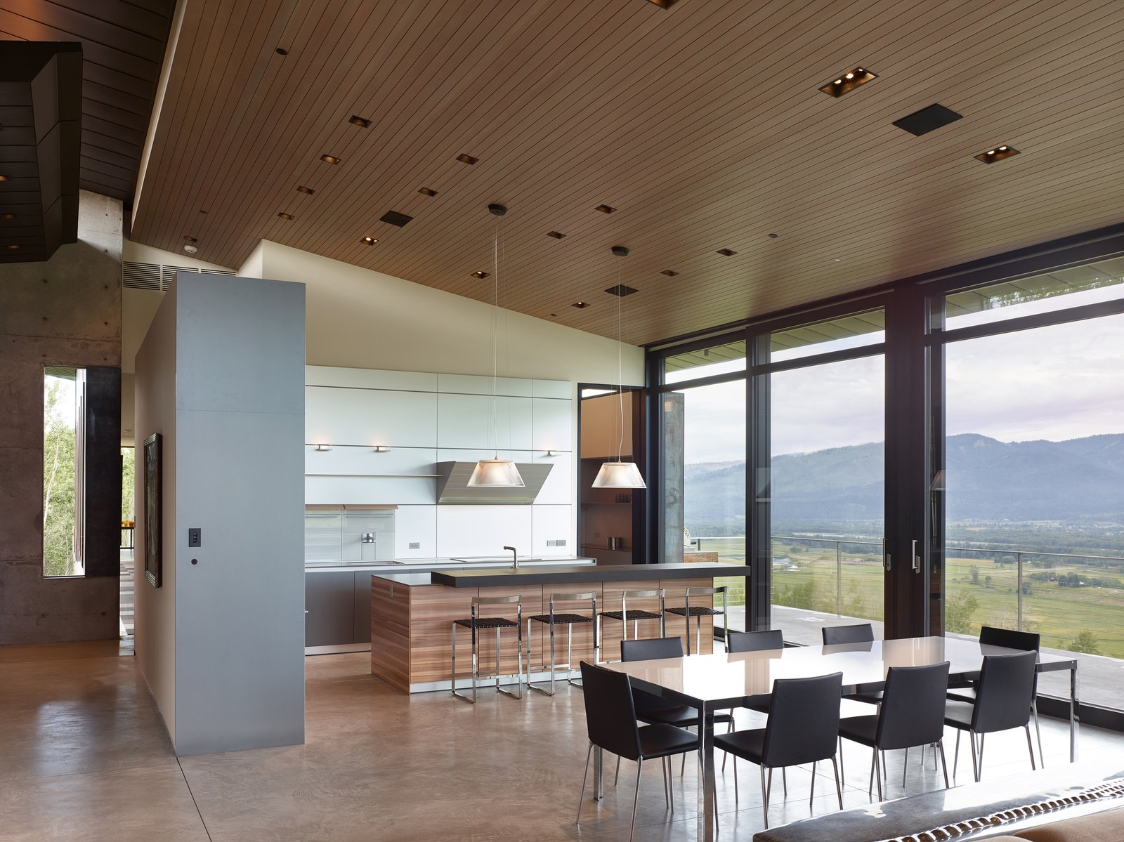 Kitchen, White Cabinet, Wood Cabinet, Concrete Floor, Pendant Lighting, and Recessed Lighting The dining area sits between the open concept kitchen and living room.   Wyoming Residence by Abramson Teiger Architects