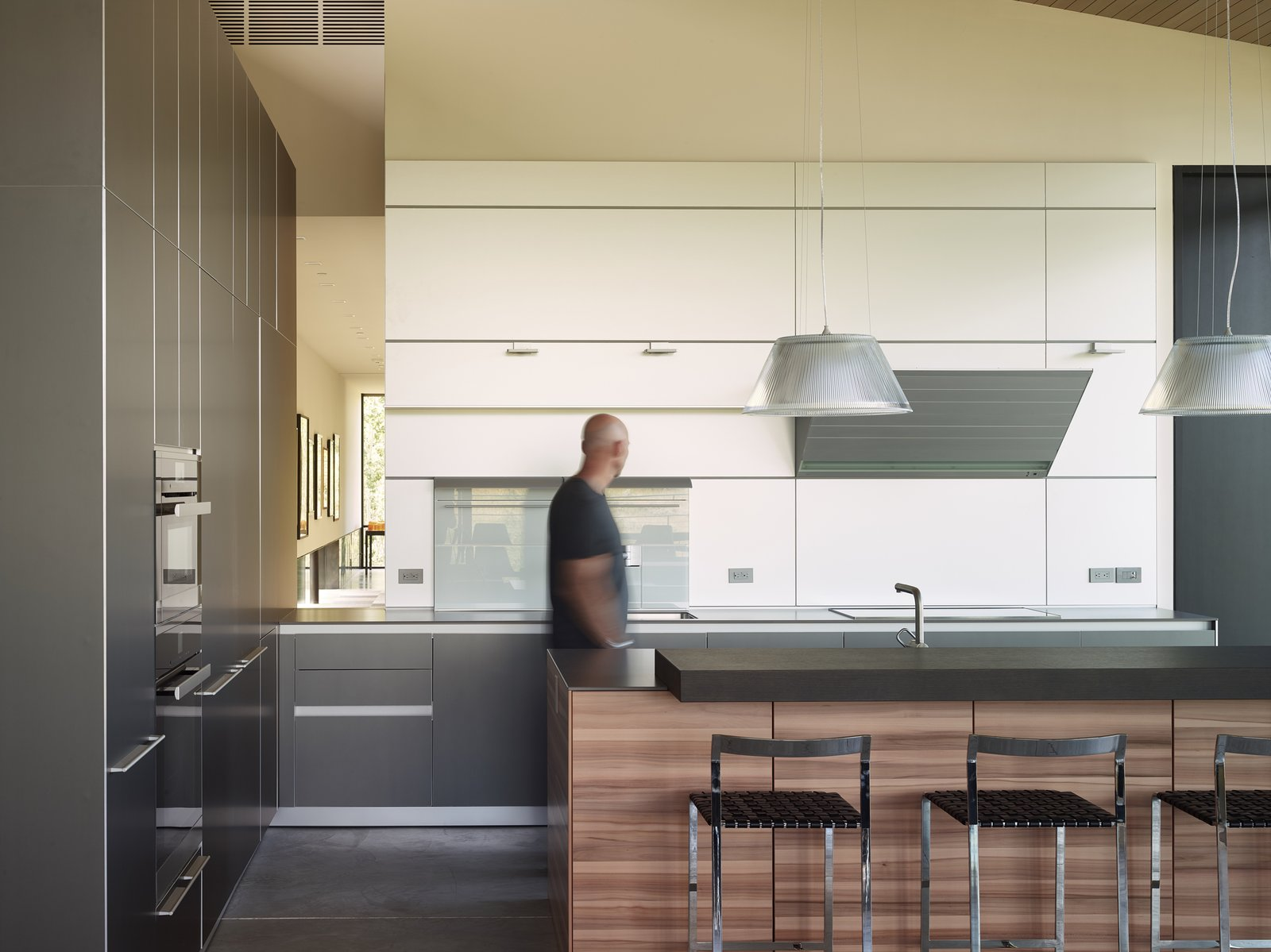 Kitchen, Wood Cabinet, White Cabinet, Pendant Lighting, Concrete Floor, Cooktops, and Wall Oven The minimal kitchen design is apportioned with tri-colored cabinets and a clever opening through that overlooks the gallery.  Wyoming Residence by Abramson Teiger Architects