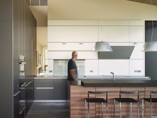 The minimal kitchen design is apportioned with tri-colored cabinets and a clever opening through that overlooks the gallery.