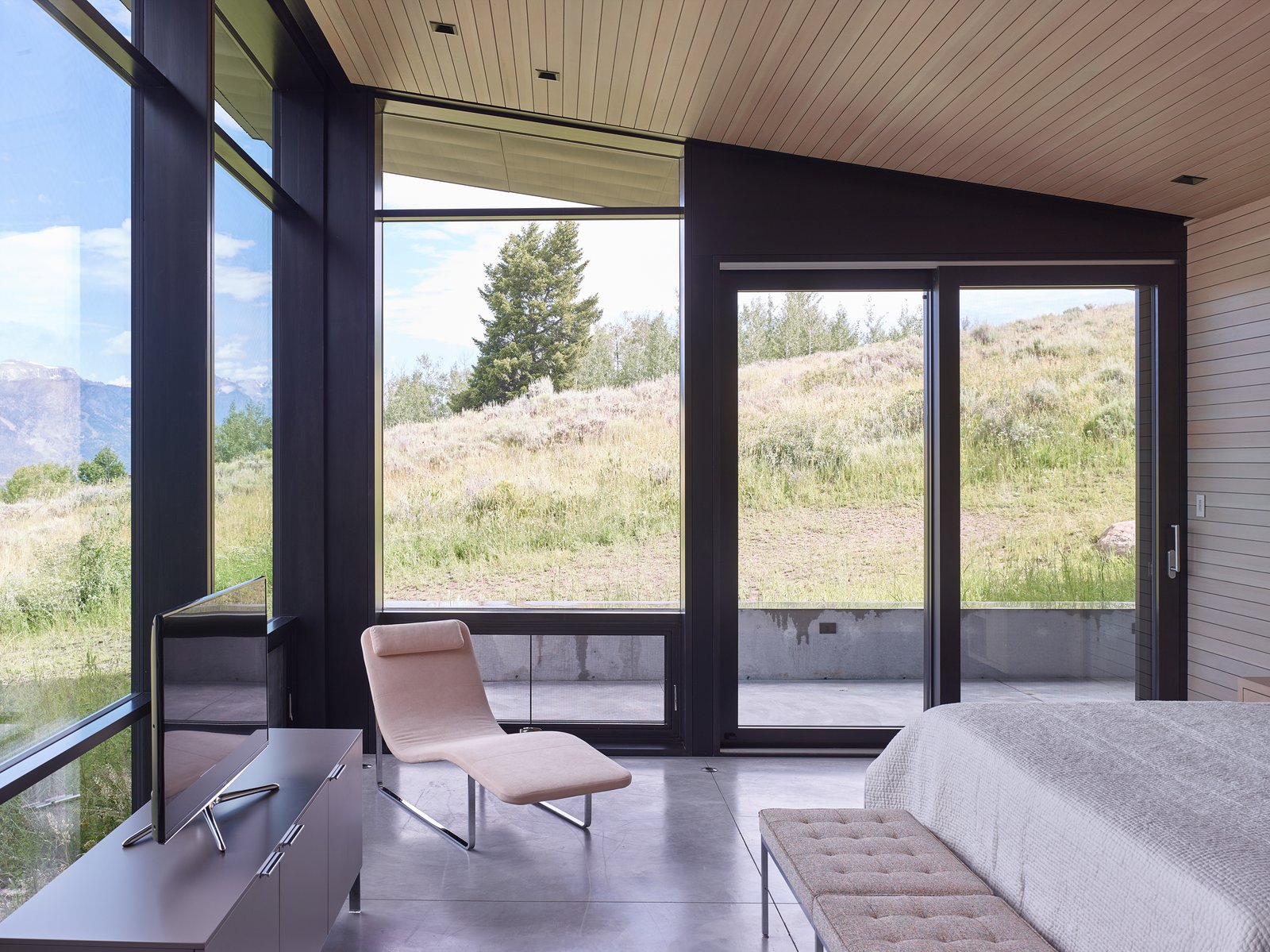 Bedroom, Bed, Chair, Concrete Floor, Bench, and Recessed Lighting The master bedroom shares in the floor-to-ceiling views, allowing symbiosis with the meadow outside.  Wyoming Residence by Abramson Teiger Architects