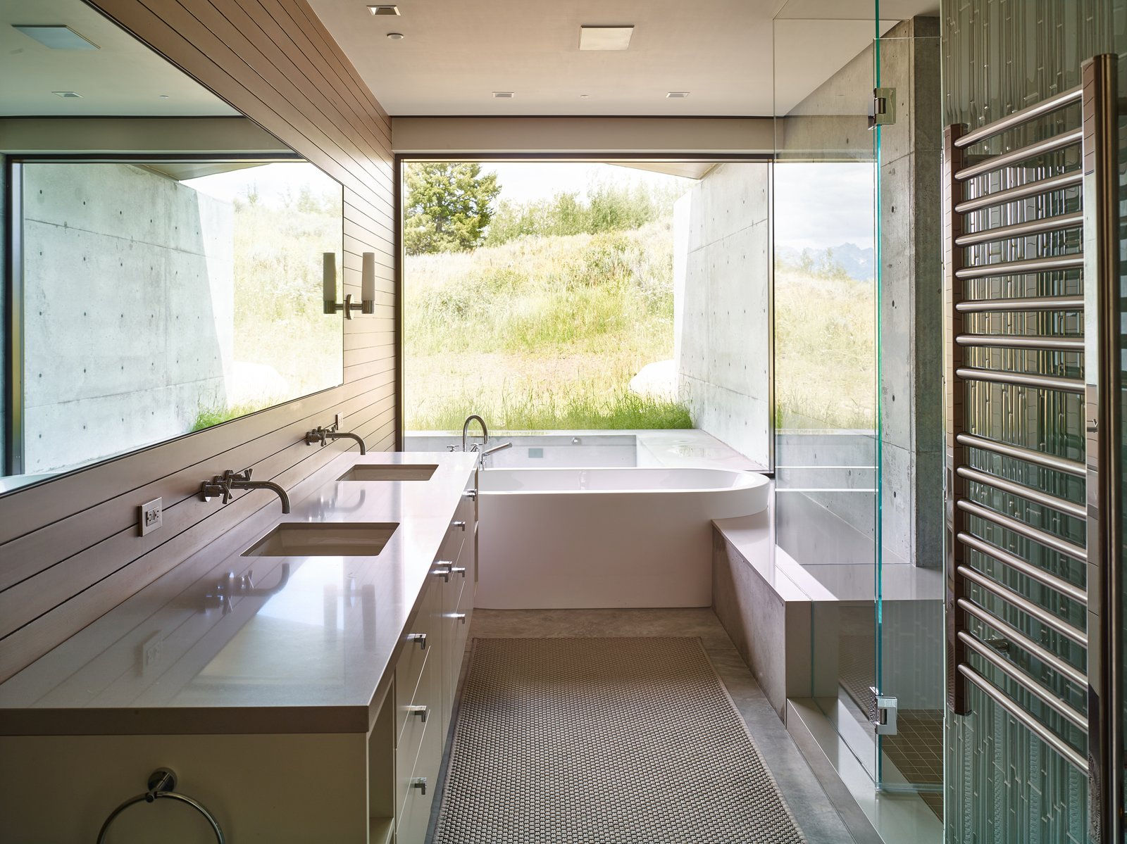 Bath Room, Freestanding Tub, Undermount Sink, Concrete Floor, Wall Lighting, Recessed Lighting, and Soaking Tub An indoor-outdoor bathroom further incorporates the exterior habitat.   Wyoming Residence by Abramson Teiger Architects