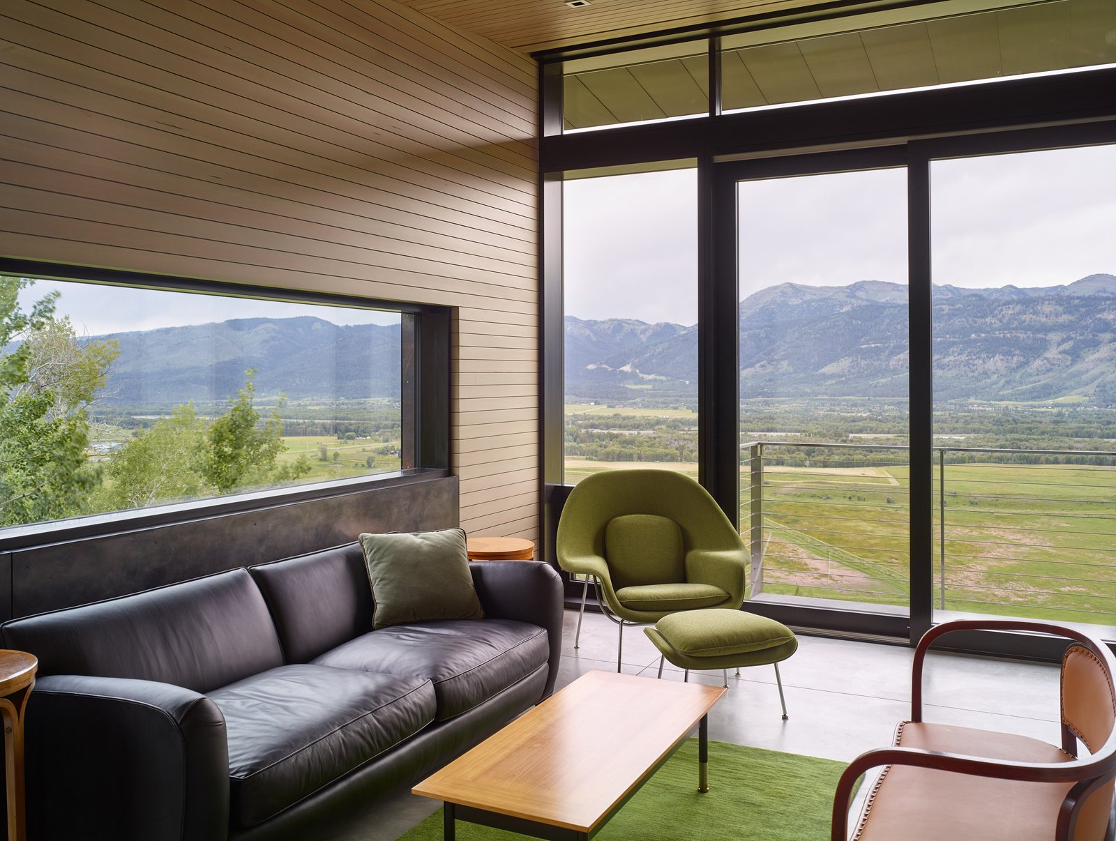 Living Room, Chair, Coffee Tables, Sofa, Recessed Lighting, Rug Floor, Concrete Floor, and End Tables Glass walls open up onto a balcony on the rear of the home.   Wyoming Residence by Abramson Teiger Architects