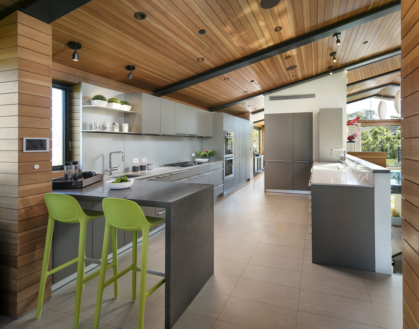 The minimal kitchen features a breakfast bar.   Cohen Residence by Abramson Teiger Architects