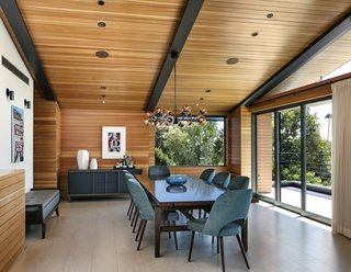 The formal dining area, also on the top level of the home, features Mid-Century furniture and lighting.