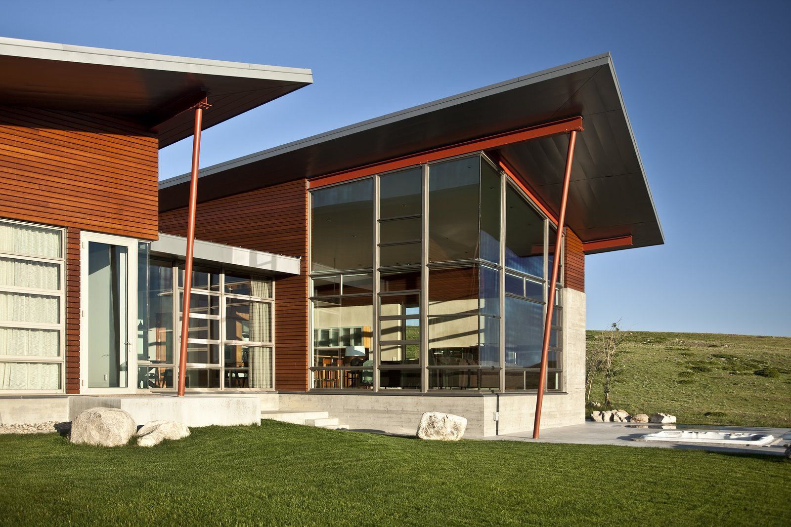 The ATA design team wanted to bring that indoor-outdoor California feeling to this home in Wyoming by highlighting its physical connection to the land. Because of the climate, however, they opted for expansive windows, not expansive openings, to capture the beautiful quality of light and the picturesque view. These windows are layered with concrete, steel and wood to converge in textural detail, accenting the sloping wings and defining a natural focal point.   Casper Residence by Abramson Teiger Architects
