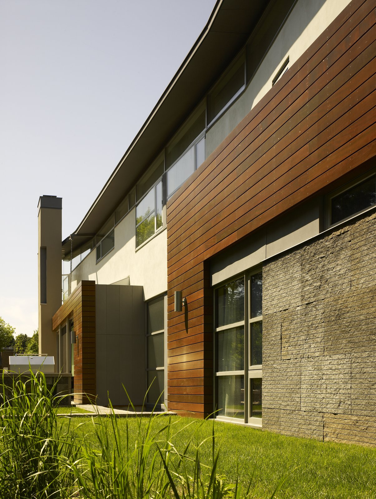 The first floor base is mostly solid, in response to the harsh Canadian winter, and is clad in layer of stone and wood.  It reads heavy and rooted to the earth. As the façade lifts up and away from the grade, it is wrapped in wood and detailed as a rain-screen, which stands proudly on the stone below it.    Davis Residence by Abramson Teiger Architects
