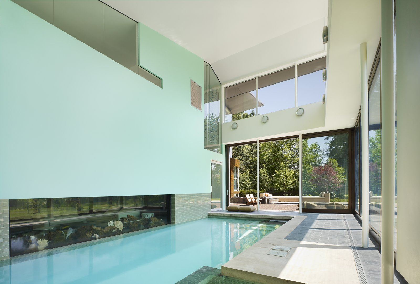 The indoor pool area opens up to the outdoor patio for year round swimming in the cold Toronto climate.  An aquarium is nestled next to the interior pool wall.   Davis Residence by Abramson Teiger Architects