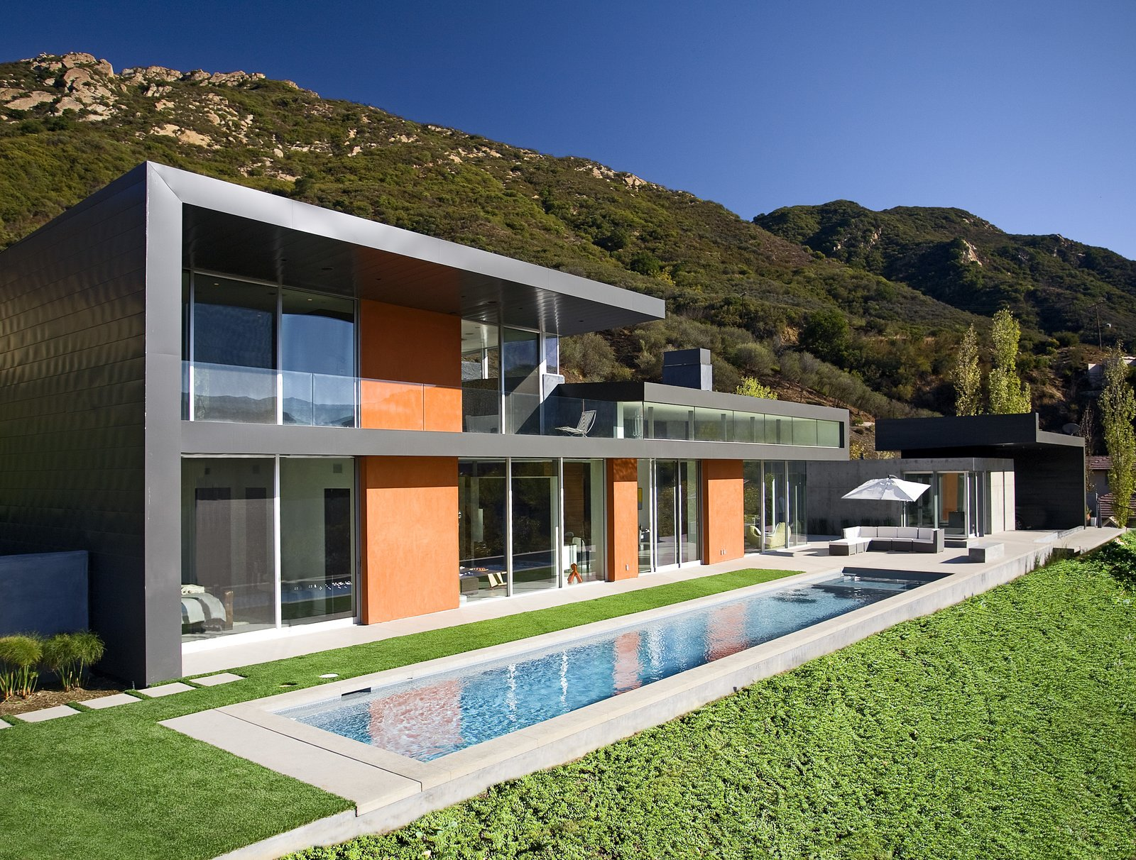 A narrow pool is nestled into the back yard next to an outdoor living area.   Lima Residence by Abramson Teiger Architects