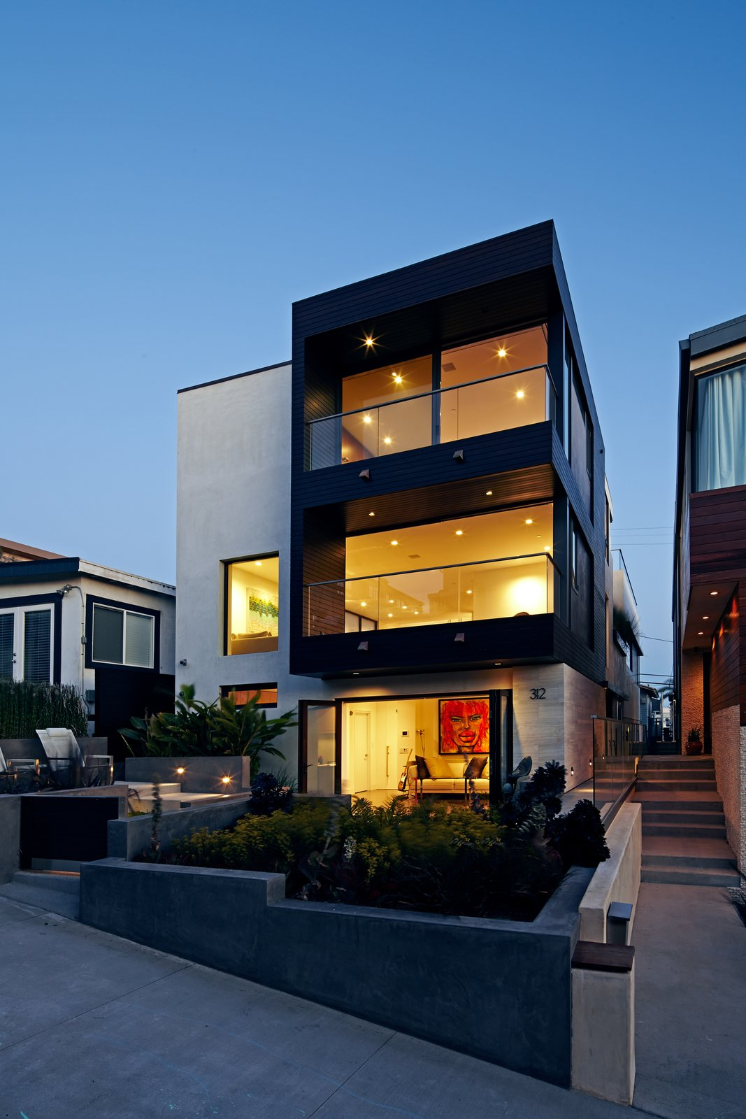 The front façade was redesigned with large openings that create a connection to the ocean views.  Accordion style glass doors were installed on the lower floor to form an indoor-outdoor space with the front garden.  The exterior palette is a subtle mix of smooth trowel stucco and honed limestone, emboldened with dark stained mahogany siding.  Perrin Residence by Abramson Teiger Architects
