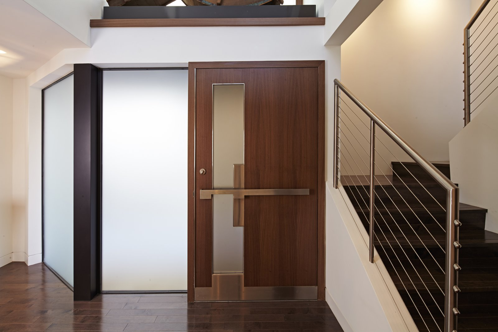 The public entry sequence pulls you through the front garden, leading to the main entry which sits on the side of the home.  A custom designed walnut and stainless steel door opens into a two-story foyer.   Perrin Residence by Abramson Teiger Architects