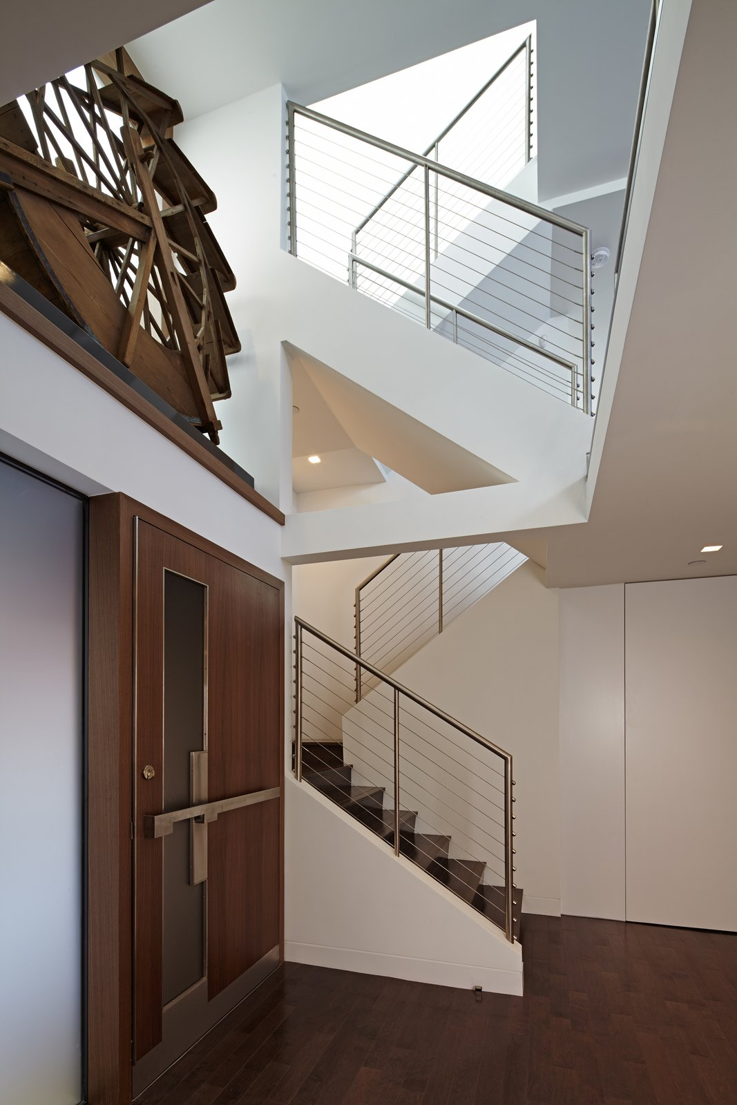 Inside, a ledge above the door holds an antique water wheel, a notable piece belonging to the Client.  This wheel is backlit with a large window adjacent to it.  Top floor skylights add dramatic light which filters down a multi-tiered staircase.      Perrin Residence by Abramson Teiger Architects