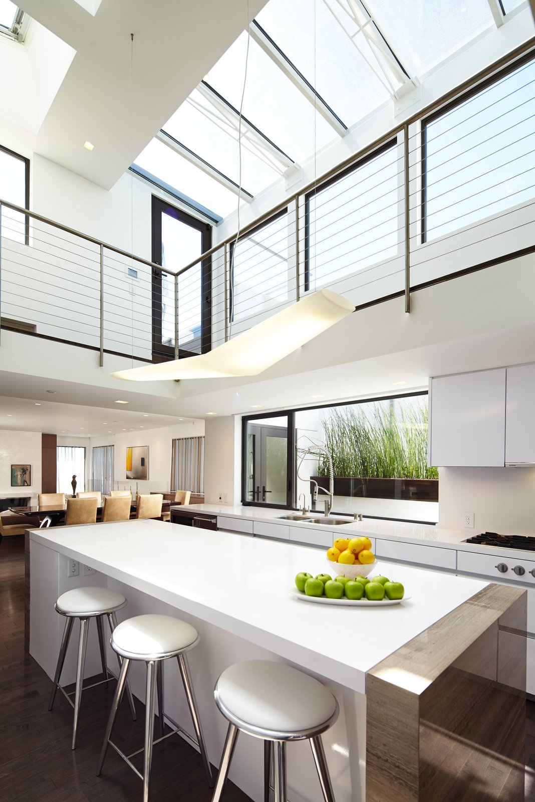 The central two-story kitchen is washed with light from multiple skylights, which also filter into the adjoining living and dining rooms.  Perrin Residence by Abramson Teiger Architects