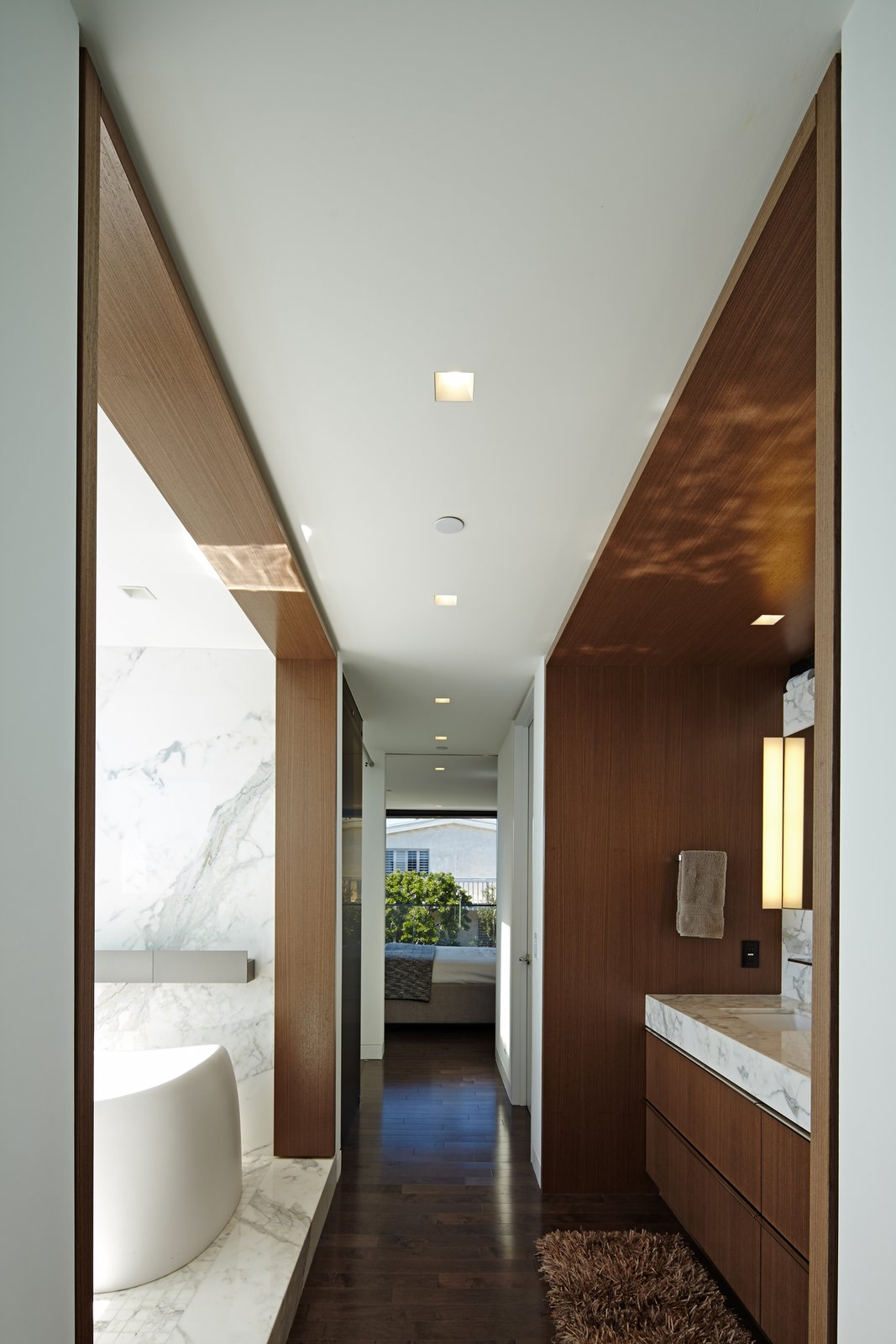 Working within the narrow structure, the master bath occupies a passage into the bedroom with intricate architectural detail.    Perrin Residence by Abramson Teiger Architects