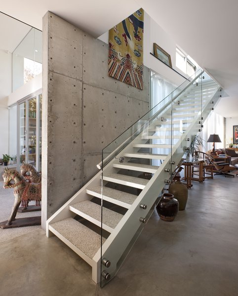 The staircase also serves as a divider between the glass half of the home, on the left, and the more solid counterpart, on the right.   Goodman Residence by Abramson Teiger Architects