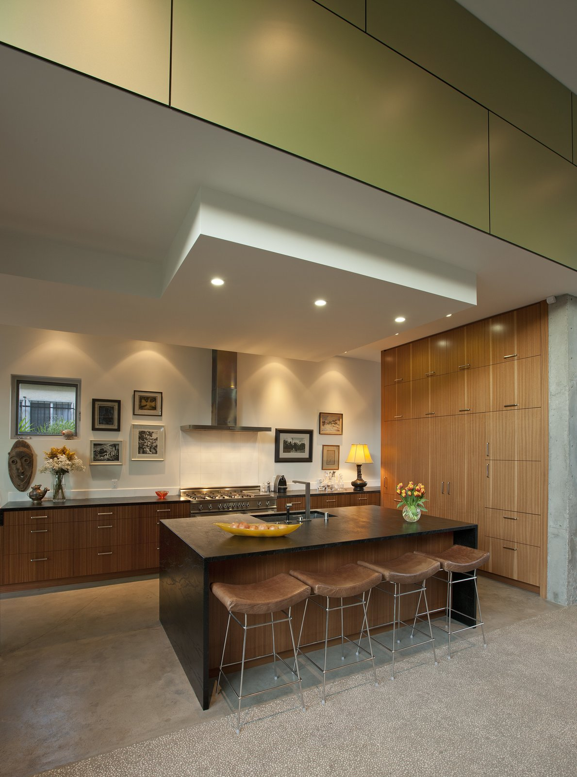 The Mid-Century style kitchen is recessed, framed in the same green Trespa panels on the exterior of the home, further incorporating an indoor-outdoor setup that is popular in Venice Beach.   Goodman Residence by Abramson Teiger Architects
