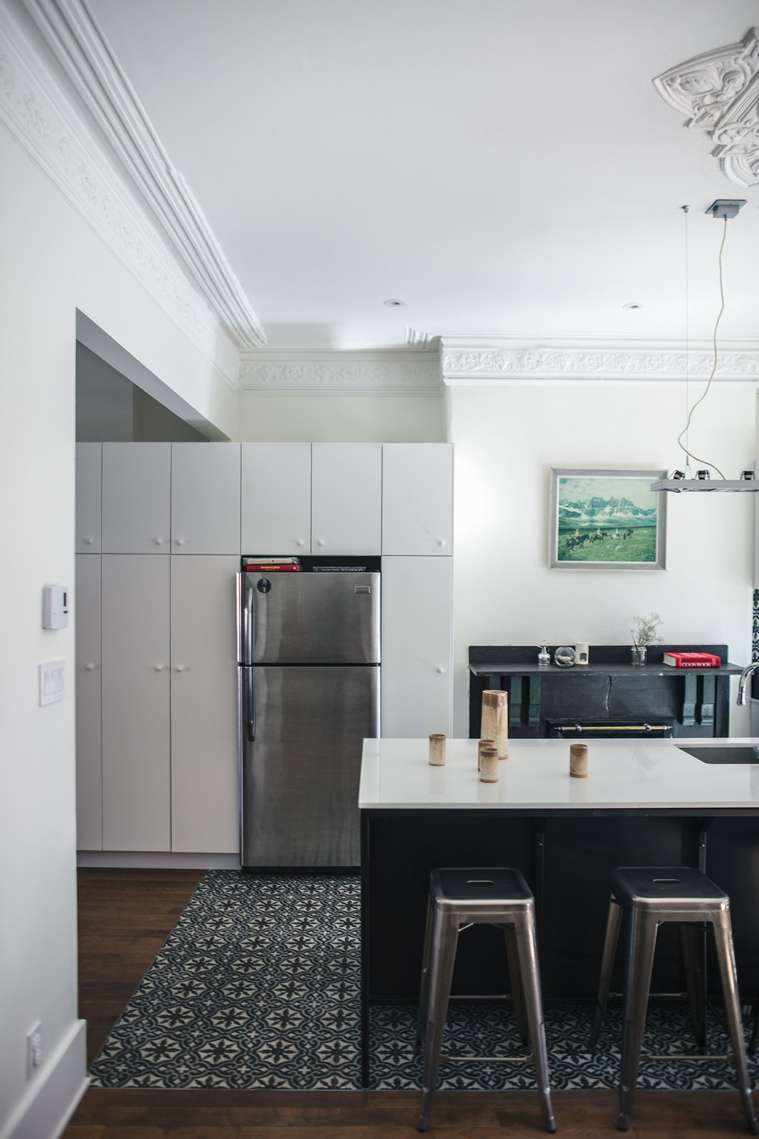 Kitchen, Refrigerator, White Cabinet, Medium Hardwood Floor, and Ceramic Tile Floor IKEA cabinets create storage around a Frigidaire refrigerator. The ornate molding maintains the historic character of the house.  Photo 3 of 6 in Historic Montreal House Meets DIY IKEA