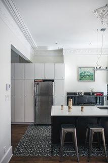 IKEA cabinets create storage around a Frigidaire refrigerator. The ornate molding maintains the historic character of the house.