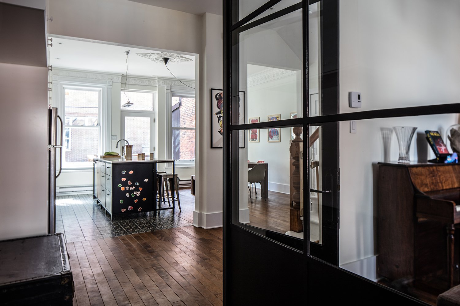 Kitchen A custom glass-and-steel partition, made by Atelier Gris, separates the living room from the kitchen while maintaining visibility between the spaces.  Photo 6 of 6 in Historic Montreal House Meets DIY IKEA