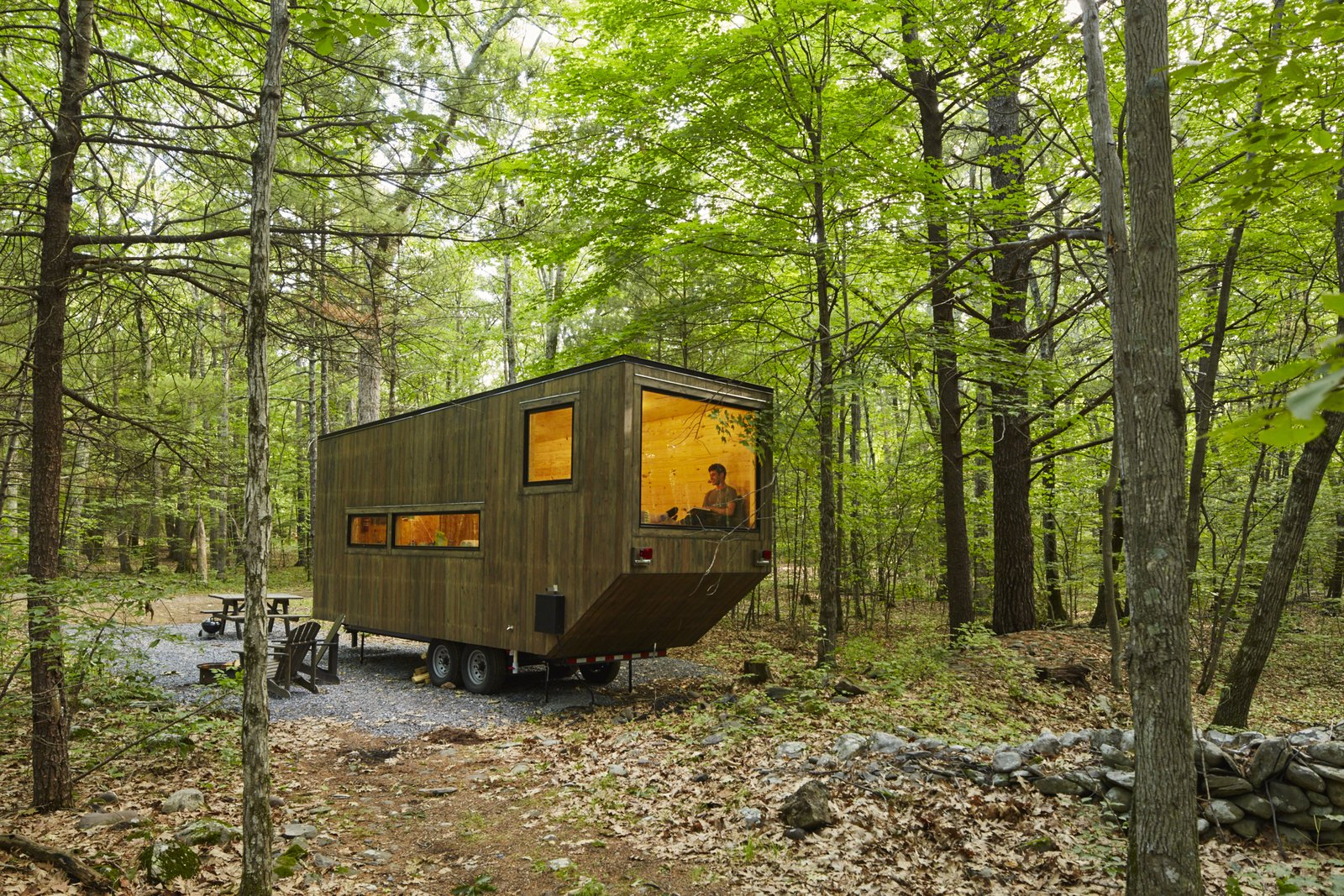 A large window is the focal point of the wheeled dwelling.  Cabin from Forgo the Tent and Give a Tiny House a Test Drive
