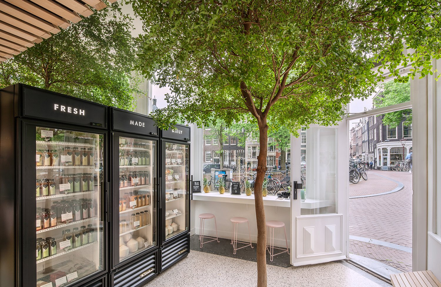 In Amsterdam's Nine Streets neighborhood, the roughly 250-square-foot shop of Cold Pressed Juicery showcases a vibrant tree in the middle of the space. Photo by Wouter van der Sar.  Photo 6 of 7 in A Tree Grows in Amsterdam
