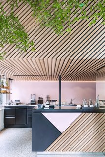 Designed by Standard Studio, the graphic store uses a palette of black and pink powder-coated metal and diagonally aligned wood slats. Photo by Wouter van der Sar.