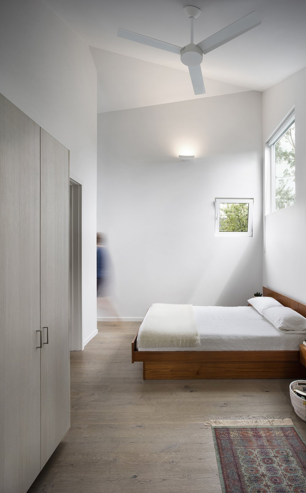 Bedroom, Bed, and Medium Hardwood Floor Highlighting the home's asymmetrical geometry, the design team decided to use a range of window sizes throughout.  Photo 7 of 8 in Quirky Toronto House Is Far From Color Shy