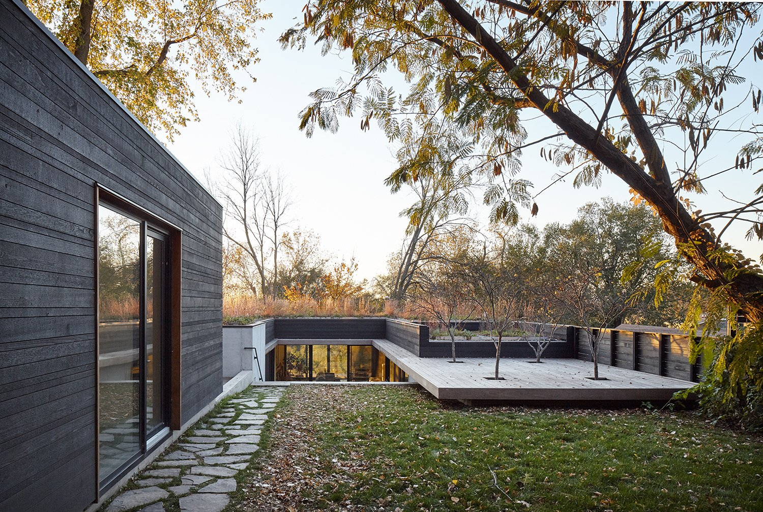 Exterior, House Building Type, and Wood Siding Material The roof, which extends into a deck, appears to float above the ground. A detached studio building is located on the site's upper level.  Outside from Nature Reigns Supreme at a Verdant Kansas City Home