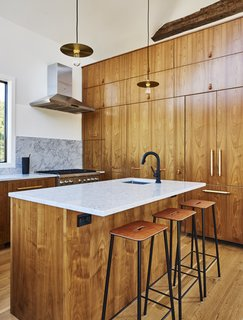 European walnut lines the custom kitchen, which is outfitted with Blum and Hafele hardware, a Brizo faucet, and pendants by Danish studio Frama. The range is Thermador.
