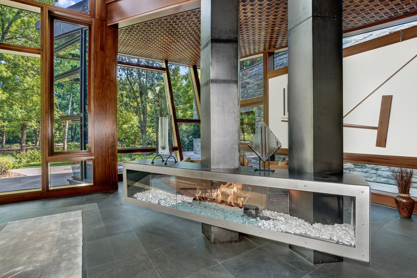 Designed by architect David Jameson in the heart of Bethesda, Maryland, this sculptural residence is filled with bespoke elements that are made up of wood, metal, stone, and glass. The centralized fireplace divides the open living space into two separate seating areas, without closing them off from one another.  97+ Modern Fireplace Ideas from Proof That a Modern Fireplace Can Be the Defining Factor of a Space