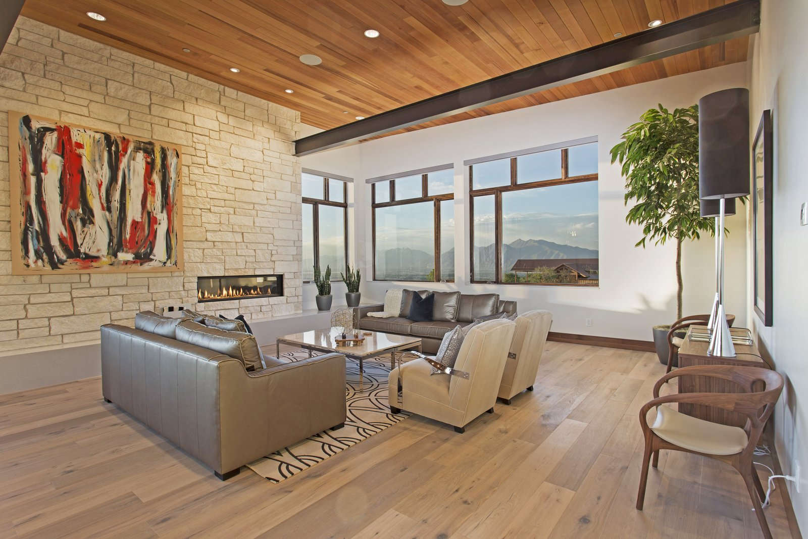 This modern mountain escape is outfitted with cutting-edge technology and sits seamlessly within the landscape of Woodland Hills, Utah. Its immense vistas are accentuated by a sleek fireplace that's surrounded by a more organic placement of stone.  97+ Modern Fireplace Ideas from Proof That a Modern Fireplace Can Be the Defining Factor of a Space