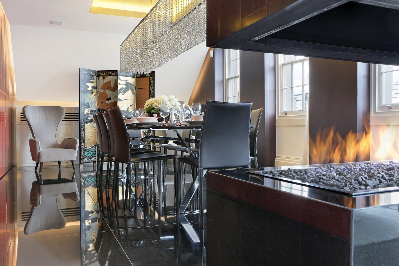 Overlooking London's St. James's Park, the penthouse of the Carlton House Terrace features 24-hour security and a private entrance with a concierge desk. Elevator access leads you to this renovated residence where the open stacked fireplace takes command of the dining room.  97+ Modern Fireplace Ideas from Proof That a Modern Fireplace Can Be the Defining Factor of a Space