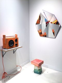 Stonefox Architect's mirror series includes five different faceted shapes in five high-gloss colors. Each mirror started with flat pieces that were fit together like a puzzle. Standing below the mirror, is Kueng Caputo's Sand Chair, formed out of Styrofoam, mortar, sand, and bright-colored pigment pastes. Also shown here is Tom Sachs's Mythologies, a mixed media art piece that mimics a speaker—and actually works.