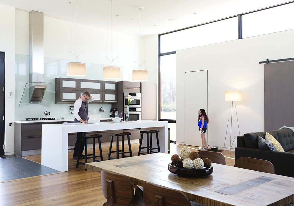 """Goldstein and his youngest daughter Sari are shown here in the open kitchen that flows into the great room, which has become the main space where the family spends time together. In the video below, Goldstein starts out by explaining how integrated smart home technology """"allows you to have an intuitive relationship with the architecture."""" He knew SAGE's wireless interface could help get the job done.  Photo 3 of 6 in See How Technology Turned This Vacation Home Into a Connected Family Hub"""