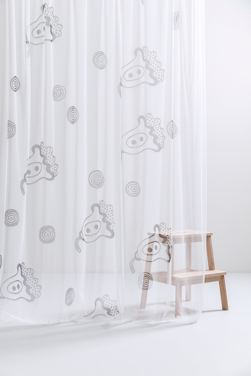 Also part of the CoopDPS collection are printed draperies that are made with an Italian woven tulle fabric. Shown here is the Provence curtain, which is inspired by the props that George and Nathalie are waving in their portrait above.  Photo 7 of 8 in Q&A With the Design Duo Behind a Playful Textile Collection