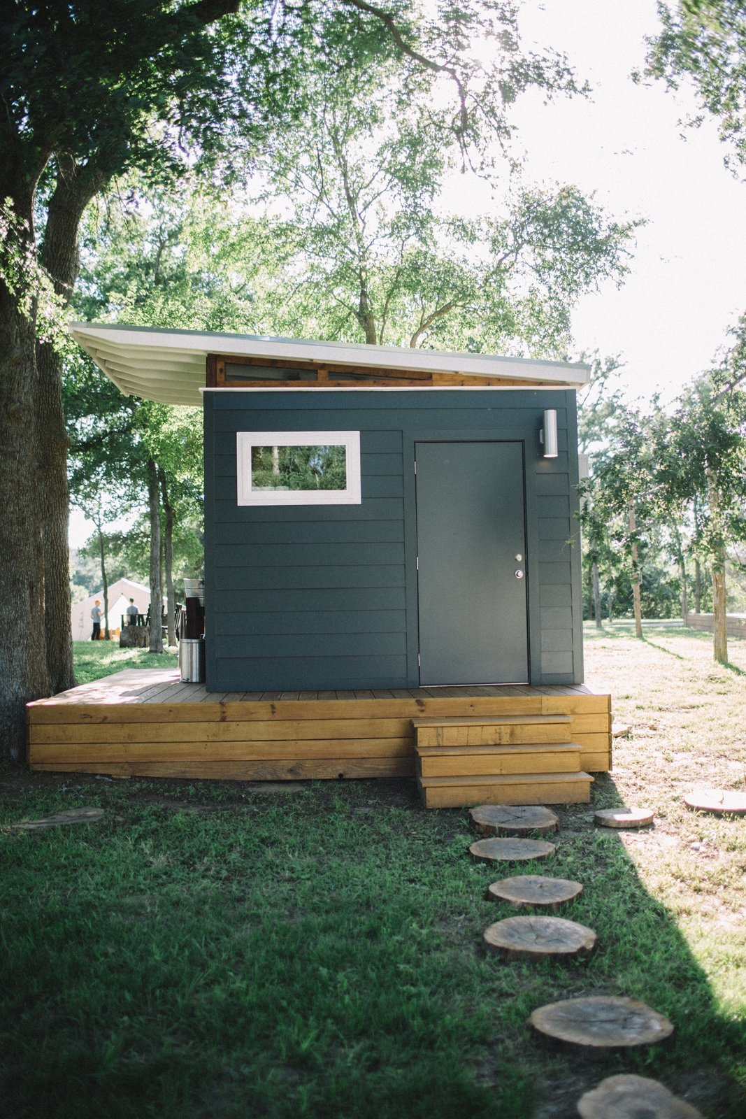 Outdoor, Trees, Grass, and Walkways Whether you're renting a yurt or hosting a small gathering, you'll have access to a modern bathhouse with a full private shower room, a separate toilet, and a washer/dryer.  Photo 5 of 8 in A Texas Camping Spot Complete With Yurts and Miniature Donkeys
