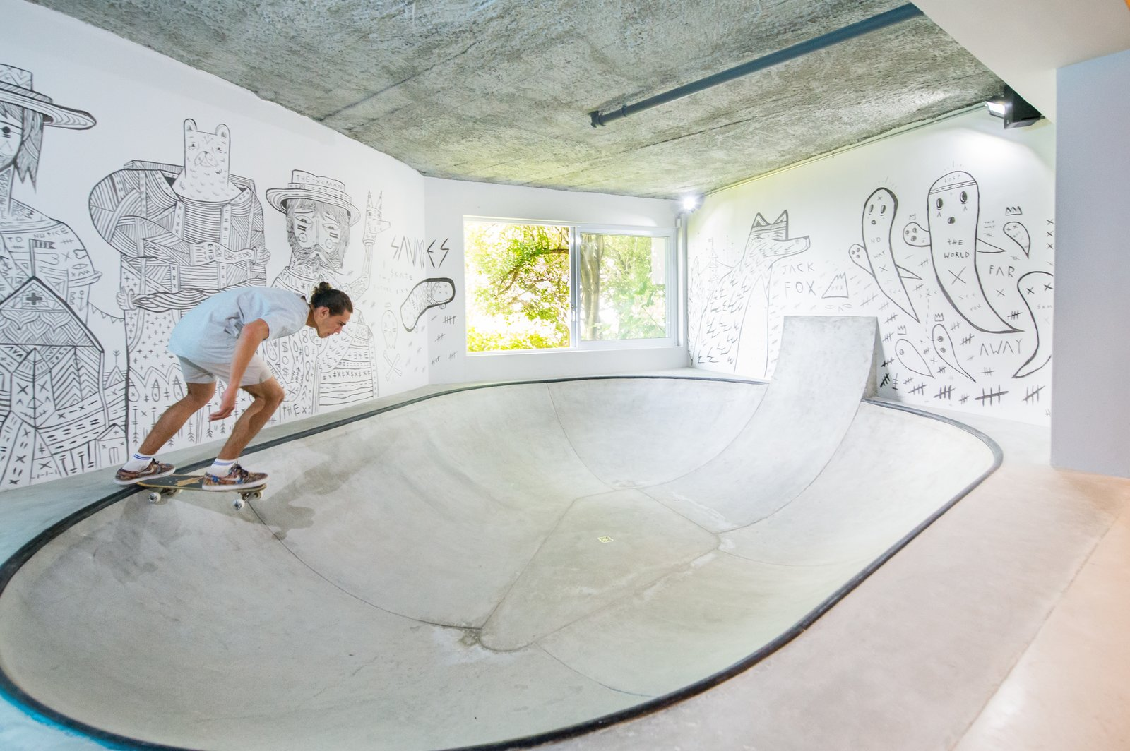 Living Room and Concrete Floor A fully functional concrete skate bowl plays a quintessential role in the layout and movement of the space. With walls lined with custom art by South African street artist Jack Fox, the playful quality of the space is achieved.  Photo 2 of 6 in A Skateboarding Devotee Gets the Lounge of His Dreams