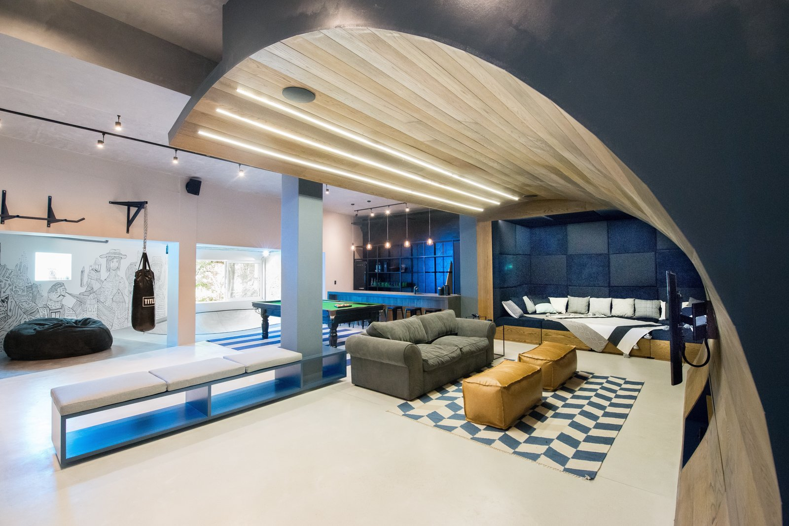 "A movie-watching paradise with a curved timber ""wave"" cascades from the ceiling to the floor. Tagged: Living Room, Sofa, and Bench.  Photo 4 of 6 in A Skateboarding Devotee Gets the Lounge of His Dreams"