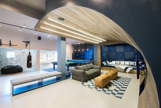 """A movie-watching seating area with a curved timber """"wave"""" cascades from the ceiling to the floor."""