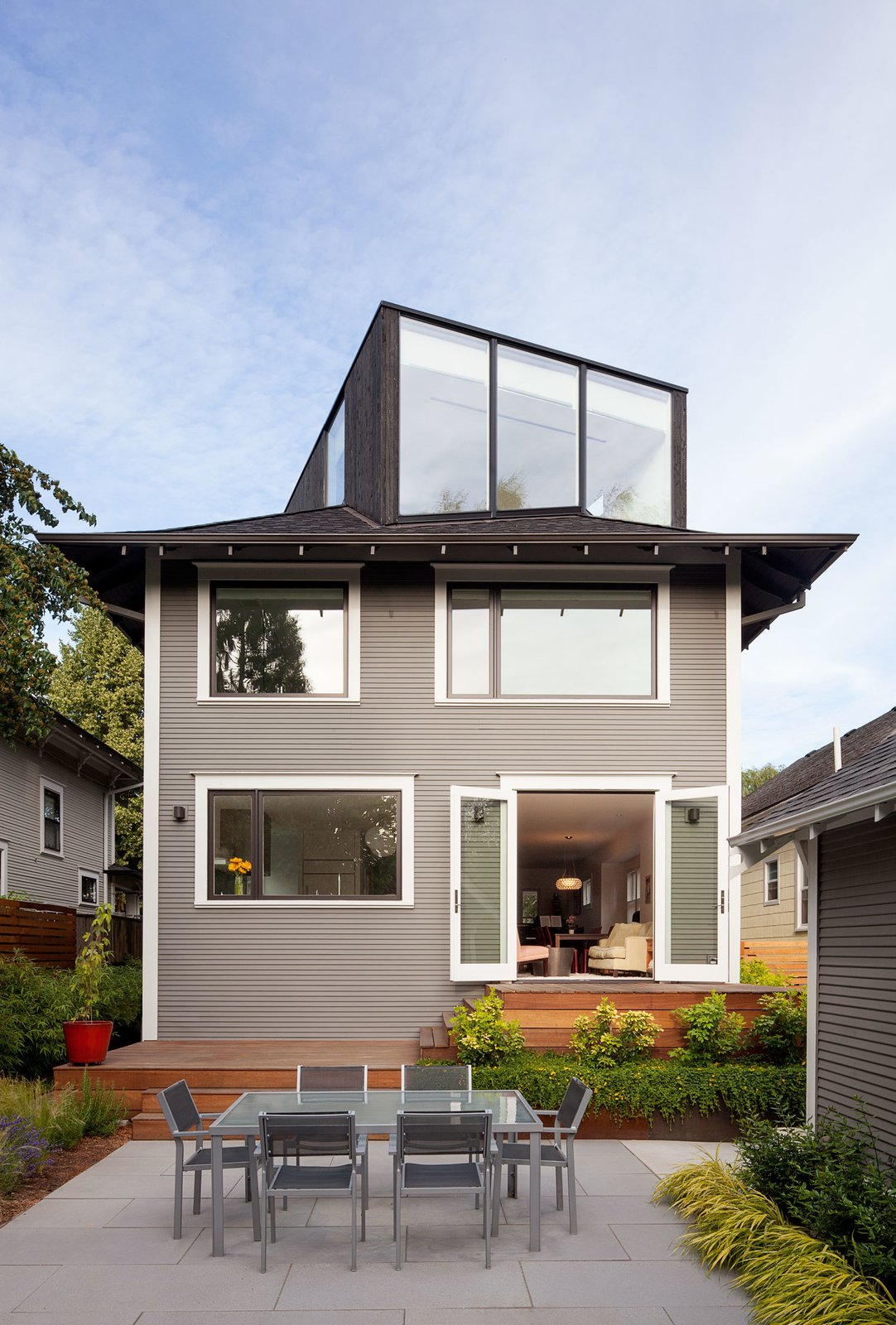 """Thomas Robinson of LEVER Architecture restored the exterior of the house in order to resurface the original wood facade, which had been covered up by vinyl siding at one point. They turned the unused attic into a """"FifthSquare"""": a box-like structure that acts as an office and mini-theater, complete with a ceiling-mounted projector and drop-down screen. The exterior of the extension is clad with charred cedar, which integrates smoothly into the asphalt shingle roof.  house pics"""