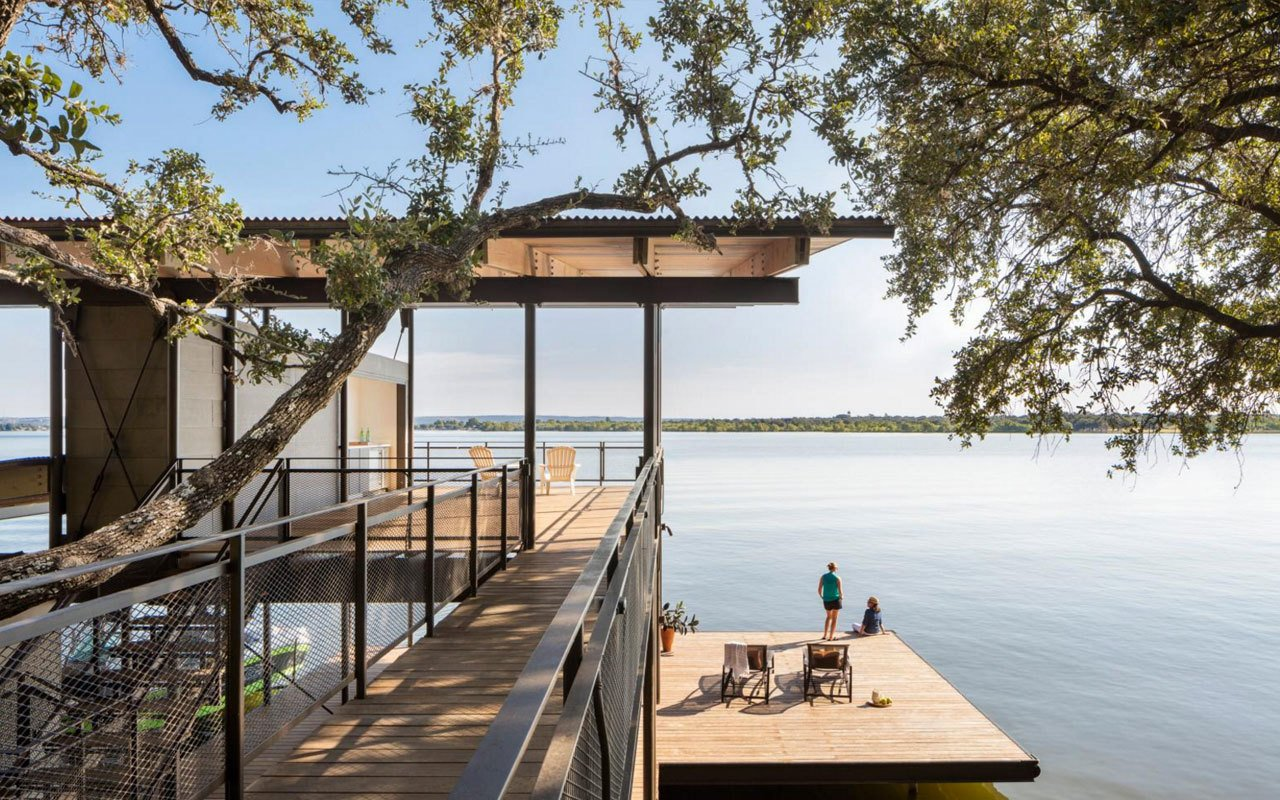 Exterior, Cabin Building Type, House Building Type, and Treehouse Building Type The three-story Blue Lake Retreat is located in Marble Falls, Texas. The residence was designed by Lake Flato Architects to integrate naturally into the steep topography. With living spaces on the top floor and four bedrooms on the two lower floors, the timber structure is connected to the hillside by a bridge and boasts a cantilevered deck that floats just above the lake.  Best Photos from Escaping to This Lakeside Retreat Would Be Like Living in a Tree House