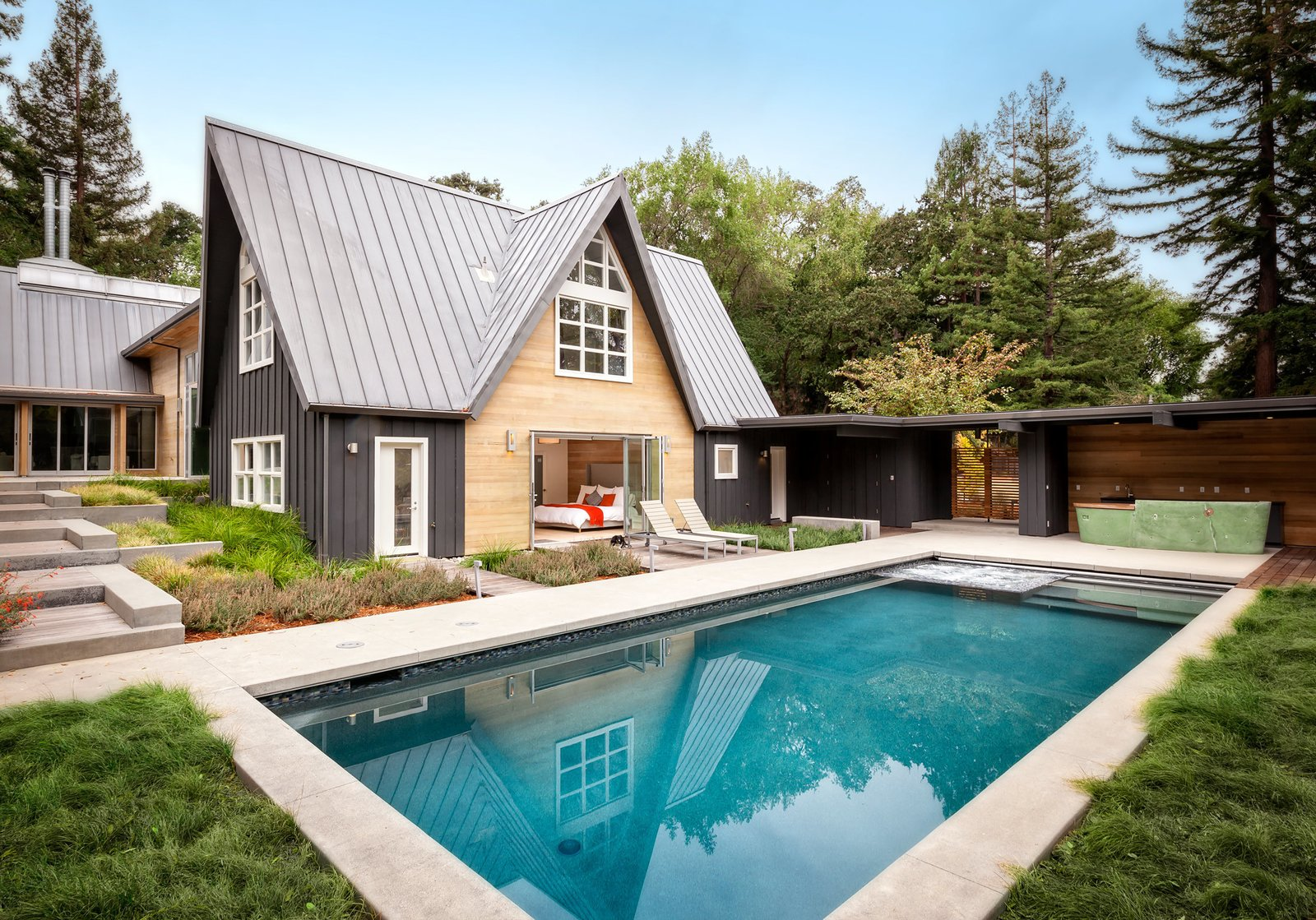 At the Dyson Residence, one of the A-frames (shown here) contains five bedrooms and looks out to a pool and outdoor bar. While one side of the house borders a tranquil creek, the other side sits alongside a nature preserve.  Modern Pool Design by Dwell from Dwell Home Tours Lands in Silicon Valley