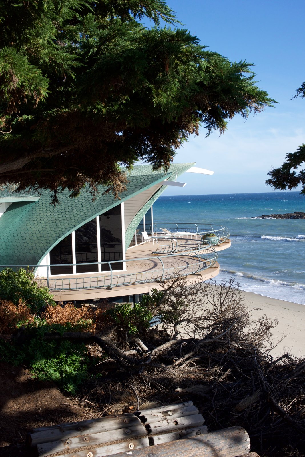The Wave House sits directly next to the Sandcastle on the sands of Malibu. When Gesner created it in 1957, the design had originally been born when he was surfing and drew the shape of the house on his surfboard with a piece of grease pencil, and would transfer it to a drawing pad and vellum when he returned to the sand. He found inspiration in the way a giant wave embraces you—and how you become a part of it. The roof is lined with copper shingles layered in a way that gives the impression of fish scales.  Photo 8 of 9 in Iconic Perspectives: Harry Gesner's Sandcastle