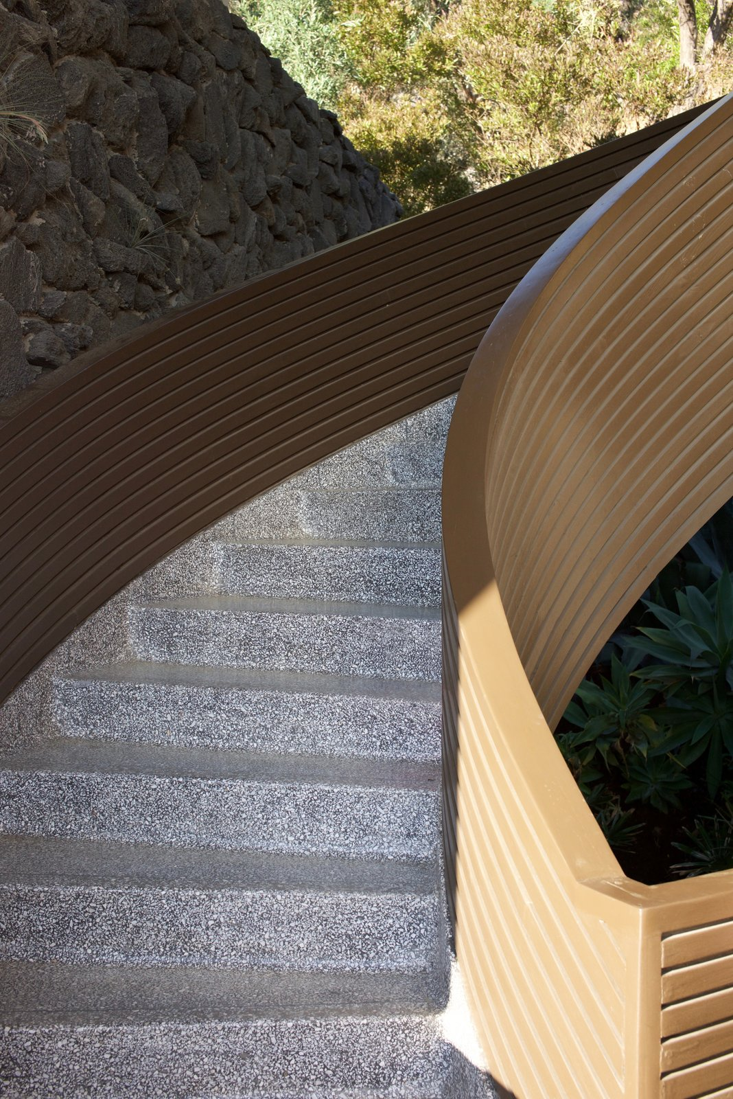 """Staircase and Concrete Tread The materials throughout the house are durable and are meant to make people feel genuinely relaxed. Mcllwee explains, """"It's not a tremendously big house, but it's mesmerizing.""""  Photo 9 of 9 in Iconic Perspectives: John Lautner's Garcia House"""