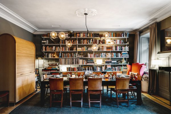 In the formal dining area, guests are invited to make themselves at home. The floor-to-ceiling bookcases create an intimate dining experience, which sits under original decorative ceiling details.  Photo 3 of 13 in A Visual Journey Through Stockholm's Hotel Ett Hem
