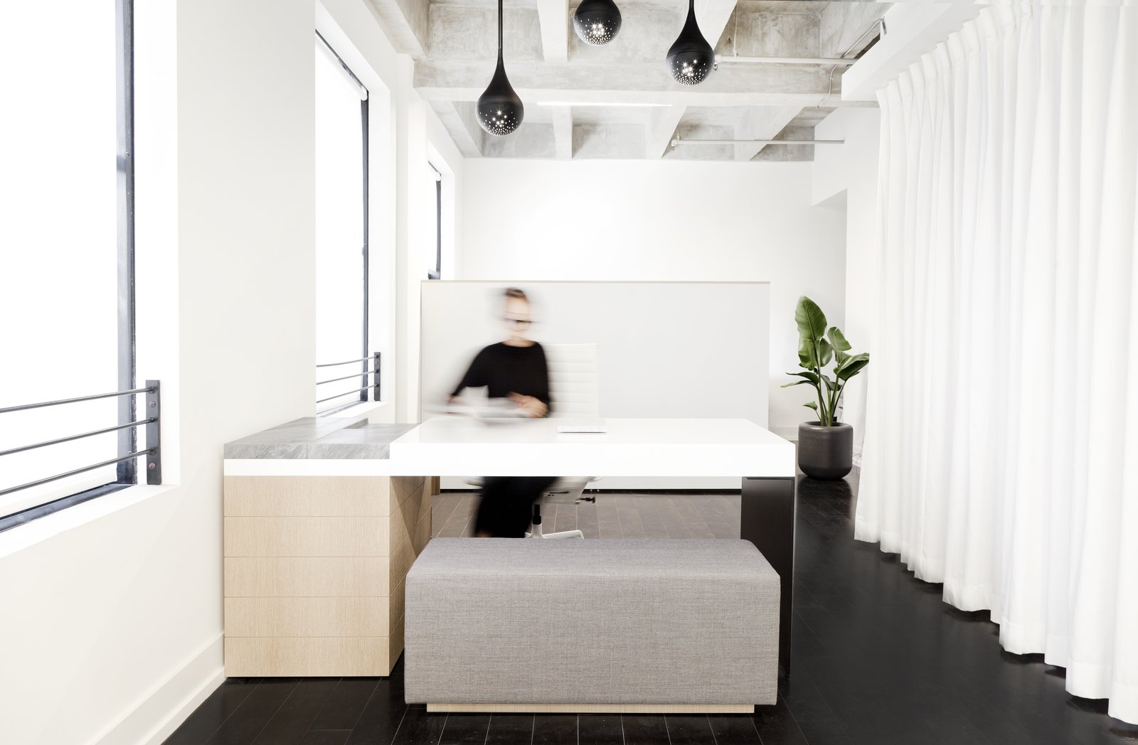 The custom appointment desk was designed and built by using a single bent sheet of aluminum, lacquered MDF, marble, and white oak. The floor-to-ceiling white textured curtain hides a built-in kitchen and brings a softness to the space.  Photo 2 of 10 in This New Jewelry Showroom Celebrates 'Made in L.A.' From Top to Bottom