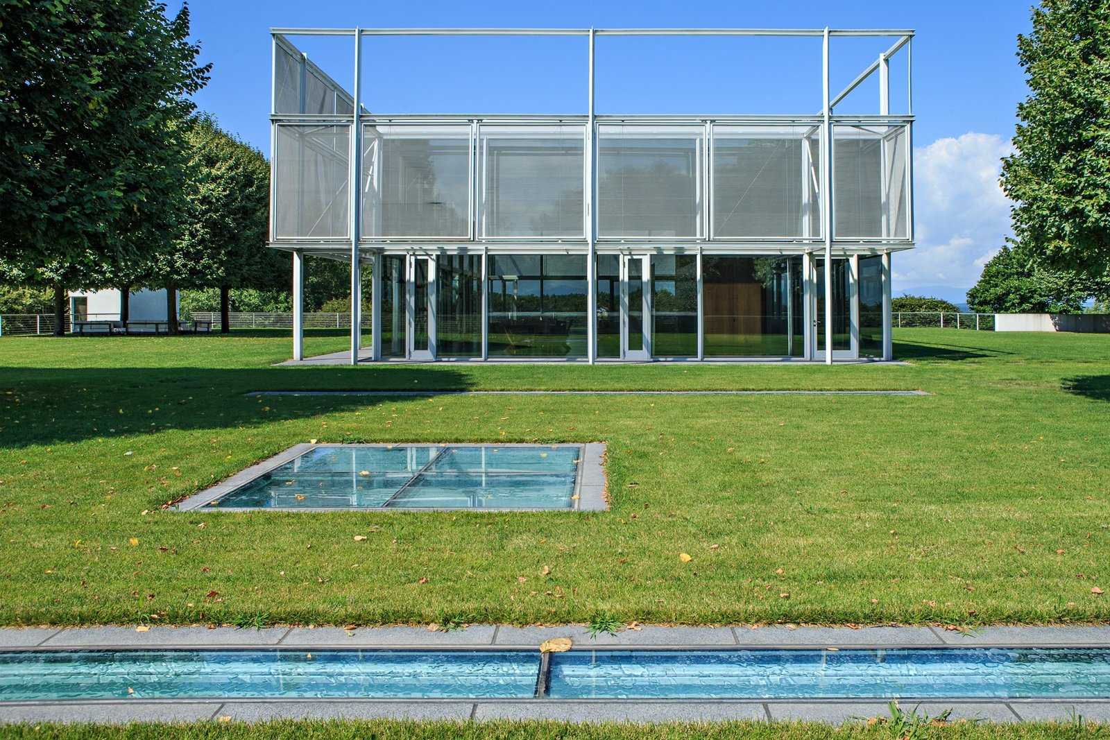 The house includes 7,000 square feet of substructure that sits on the underside of the hill from one side, and is open to the sky on the other. The glass plates seen at the forefront of this image serve as skylights to the substructure, which includes an indoor pool, mudroom, library, kitchen, gym, media room, and a walk-in cheese locker and wine room.  Photo 4 of 15 in A Thomas Phifer-Designed Glass-and-Steel Masterpiece For Sale