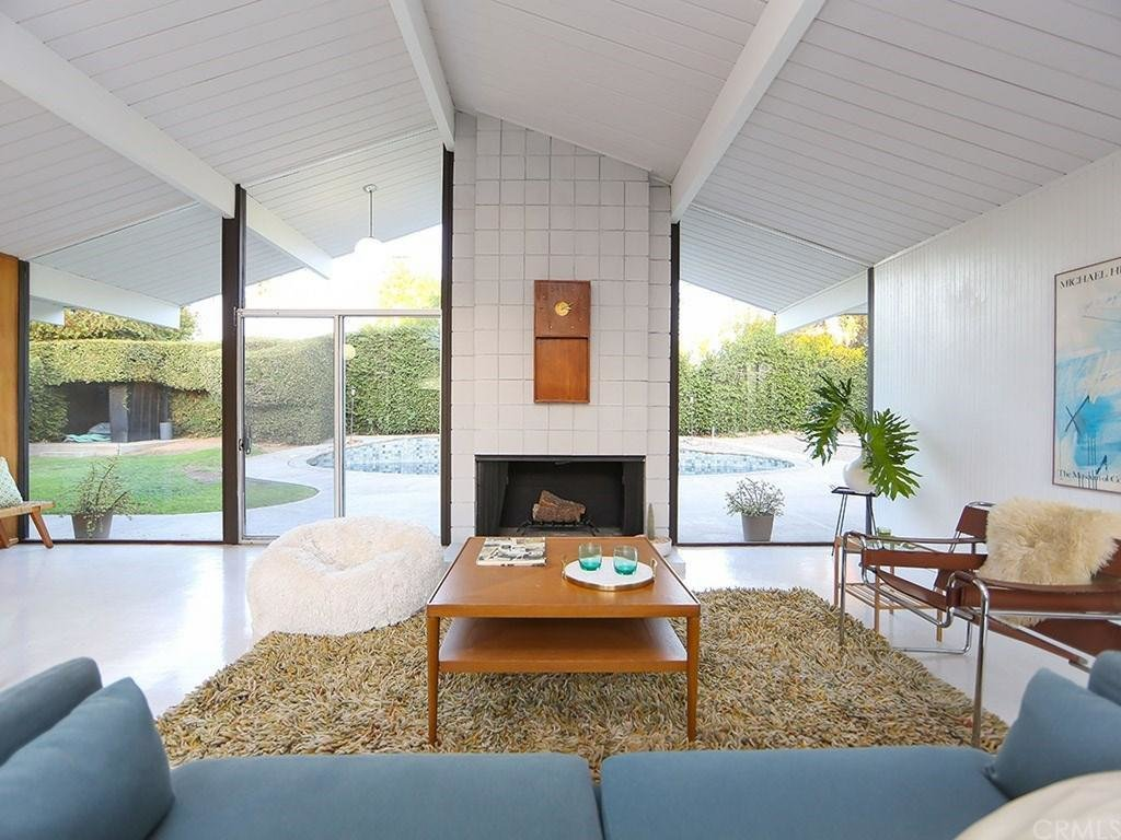 In the living space, which looks past a fireplace and out to a pool, sits under original beamed ceilings in a characteristic A-frame shape.  Mid century modern from This Quintessential Eichler Will Hit All Your Midcentury Goals—and It's For Sale